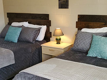 Image of made beds inside motel room with new, wooden headboards